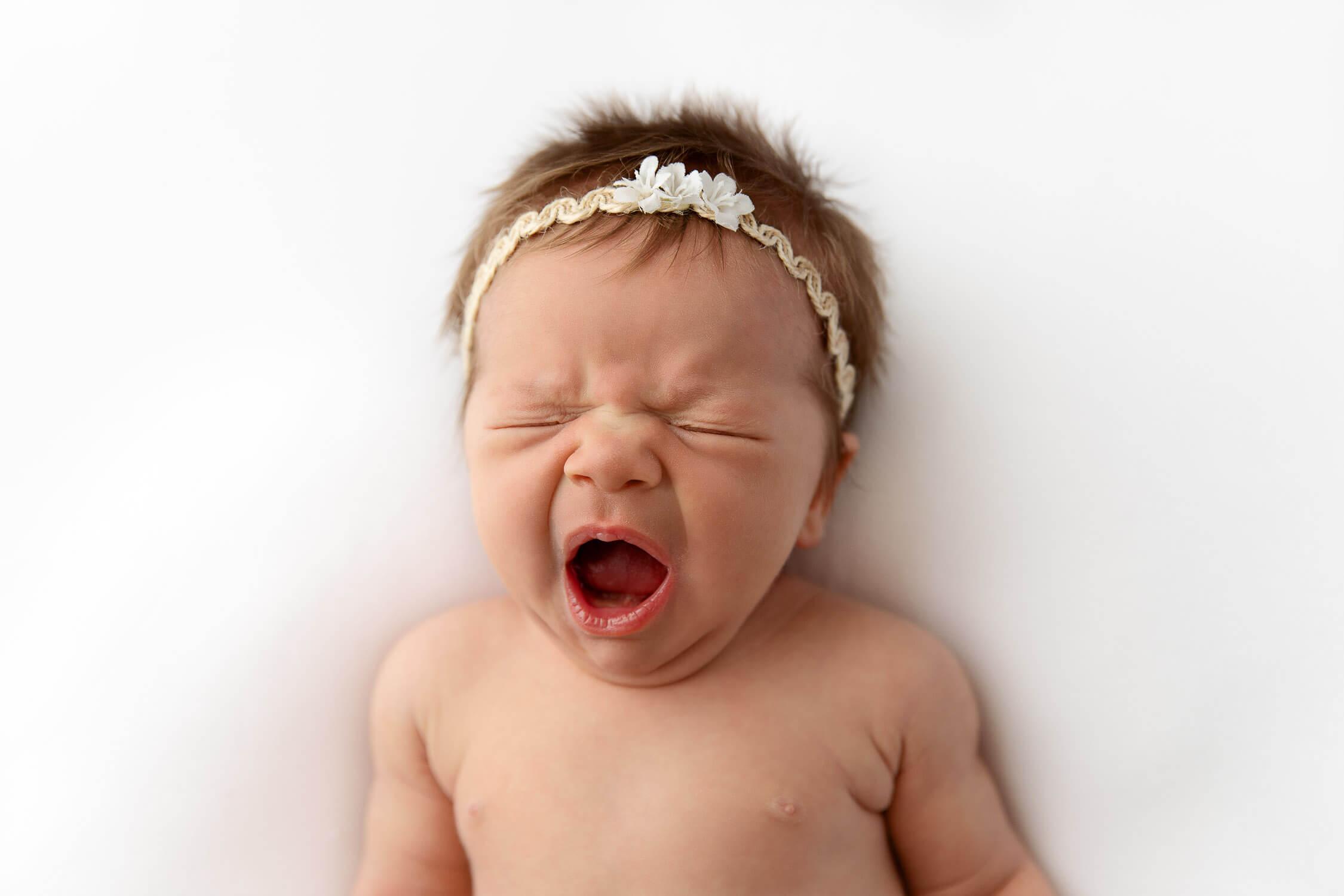 closeup of newborn baby girl yawning on a white blanket