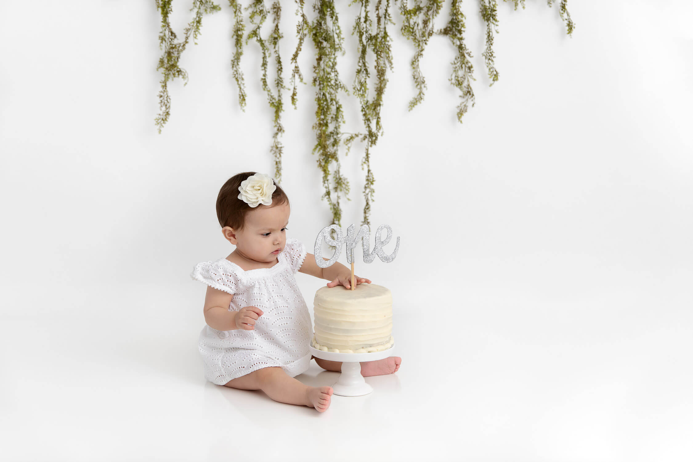 baby girl wearing white dress sitting with her smash cake that has a glitter