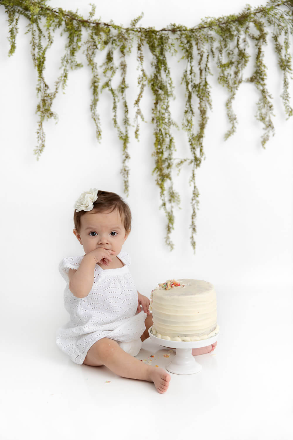 1 year old girl wearing a white dress sitting with her smash cake with greenery hanging in the background