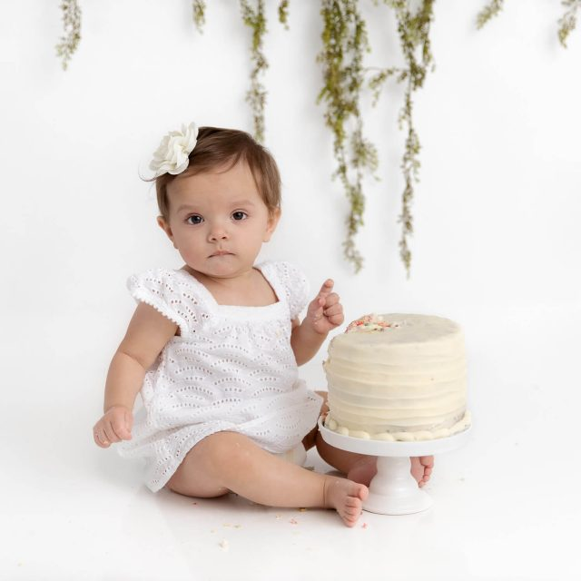 1 year old baby girl wearing a white dress in a white studio with a smash cake and greenery hanging in the background