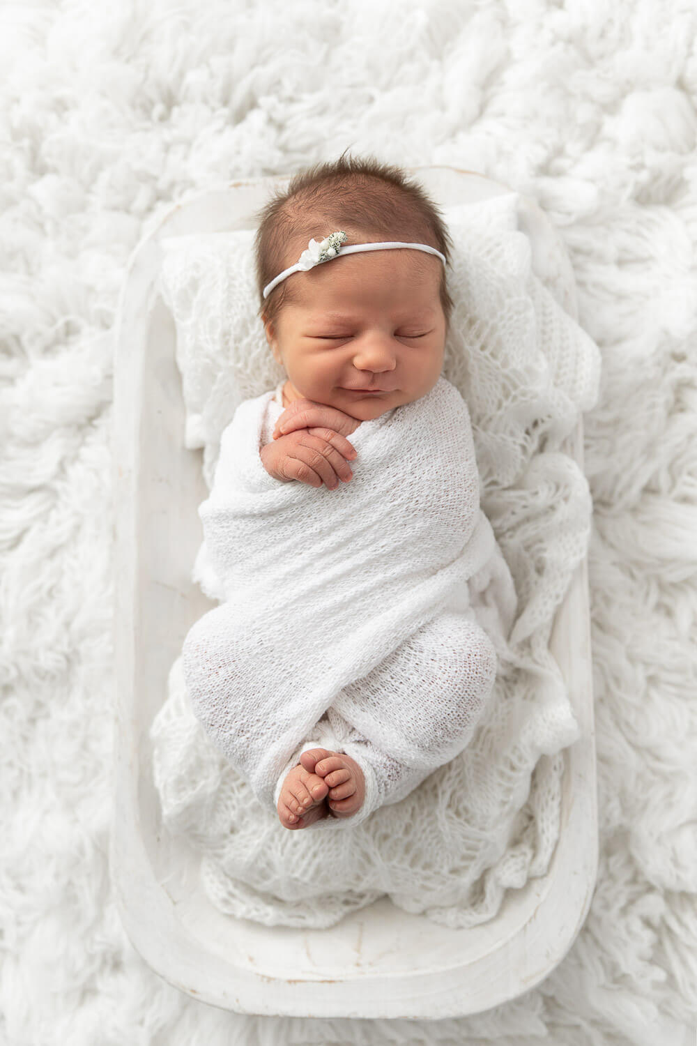 newborn baby girl wrapped in white cloth laying on a white dough bowl surrounded by white fur