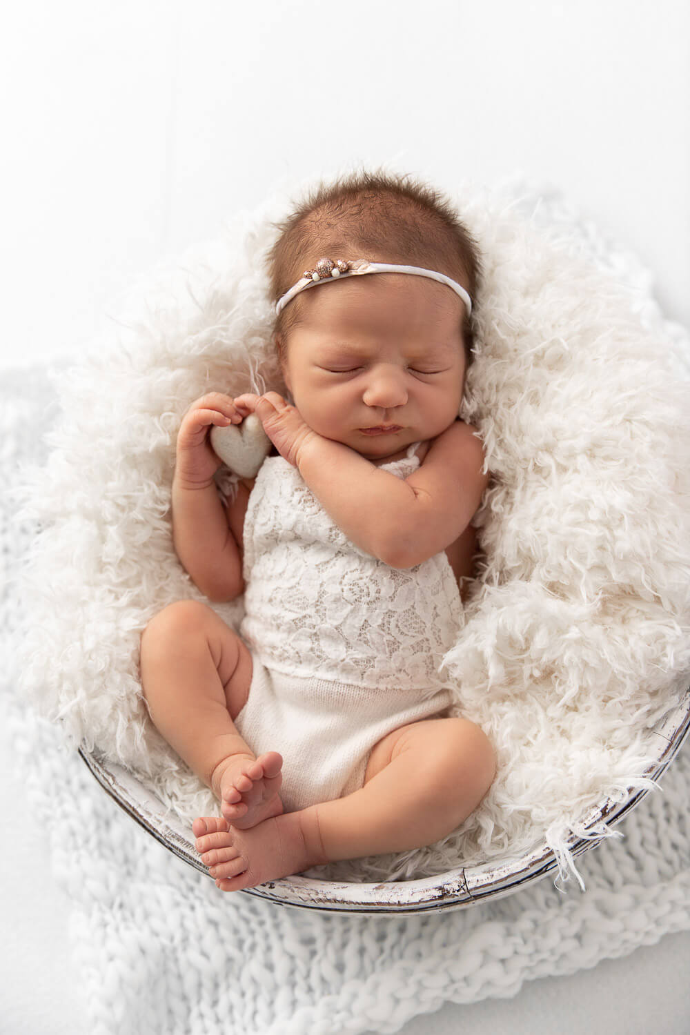 newborn baby girl wearing a white lace romper laying in a bucket with white fur holding a white felt heart
