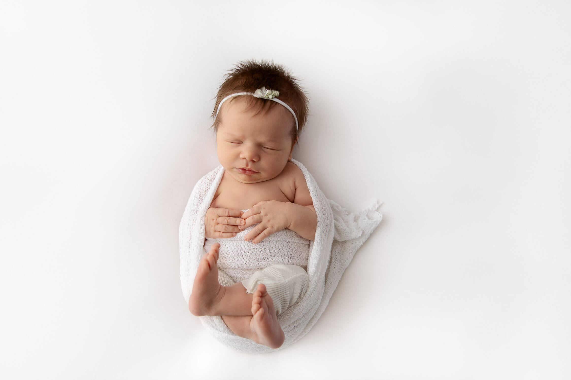 newborn baby girl wrapped curled up with white stretch fabric on a white beanbag