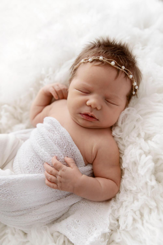 newborn girl wrapped in white blanket sleeping on white fur