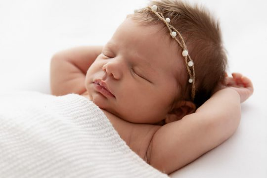 backlit newborn baby girl sleeping under a white blanket with arms raised over her head