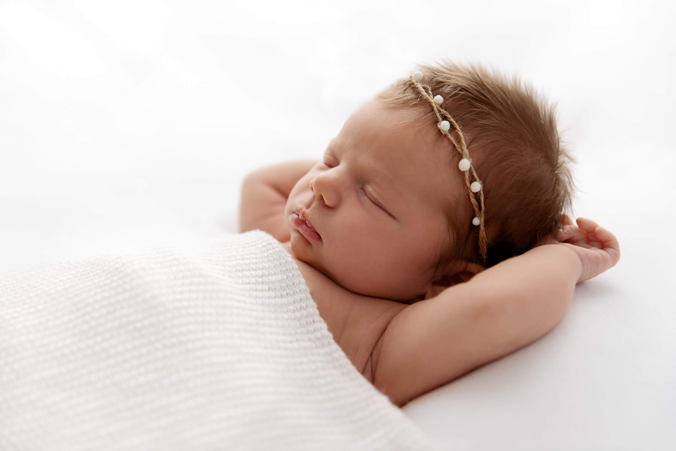 backlit newborn baby girl sleeping under a white blanket with arms over head