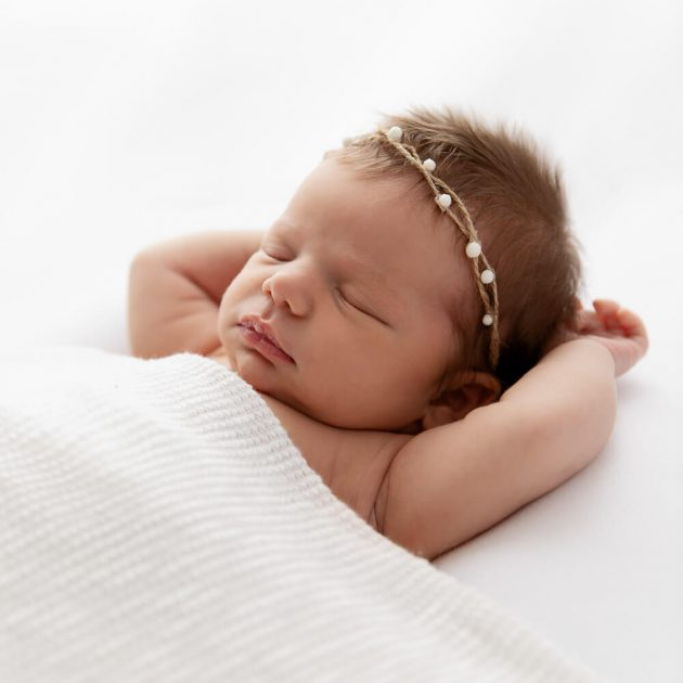 newborn baby girl sleeping under a white blanket with arms over her head backlit with bright white light