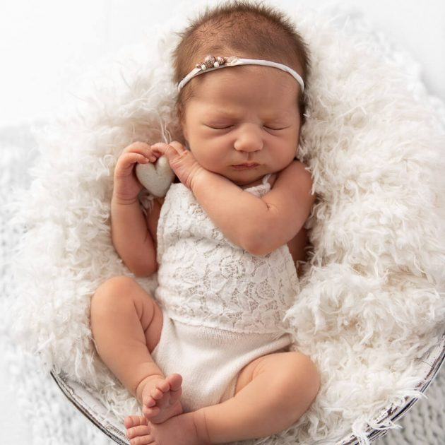 newborn baby girl wearing a white lace romper in a white fur bucket holding a white felt heart