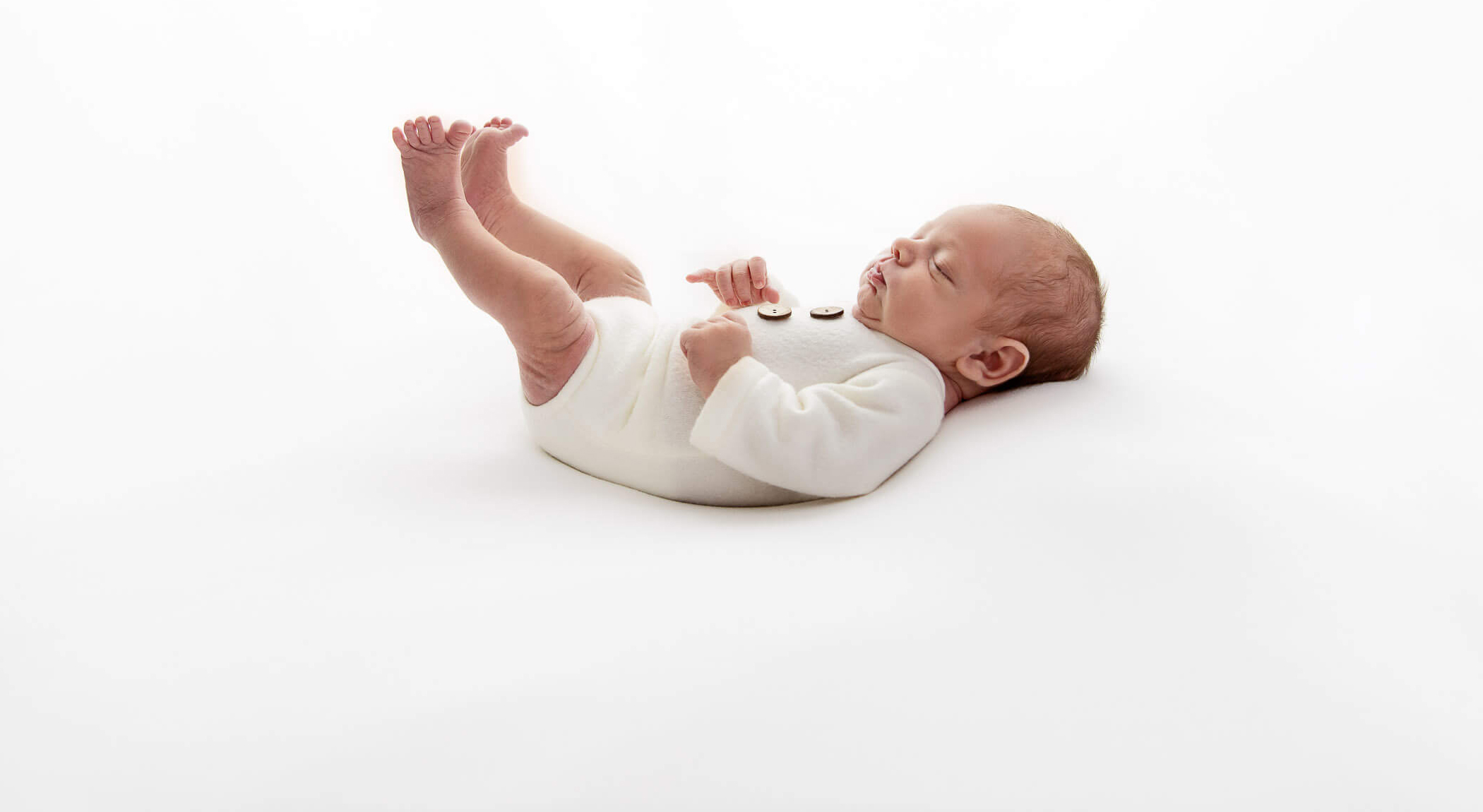 backlit newborn baby boy in white romper laying on back with legs and toes outstretched