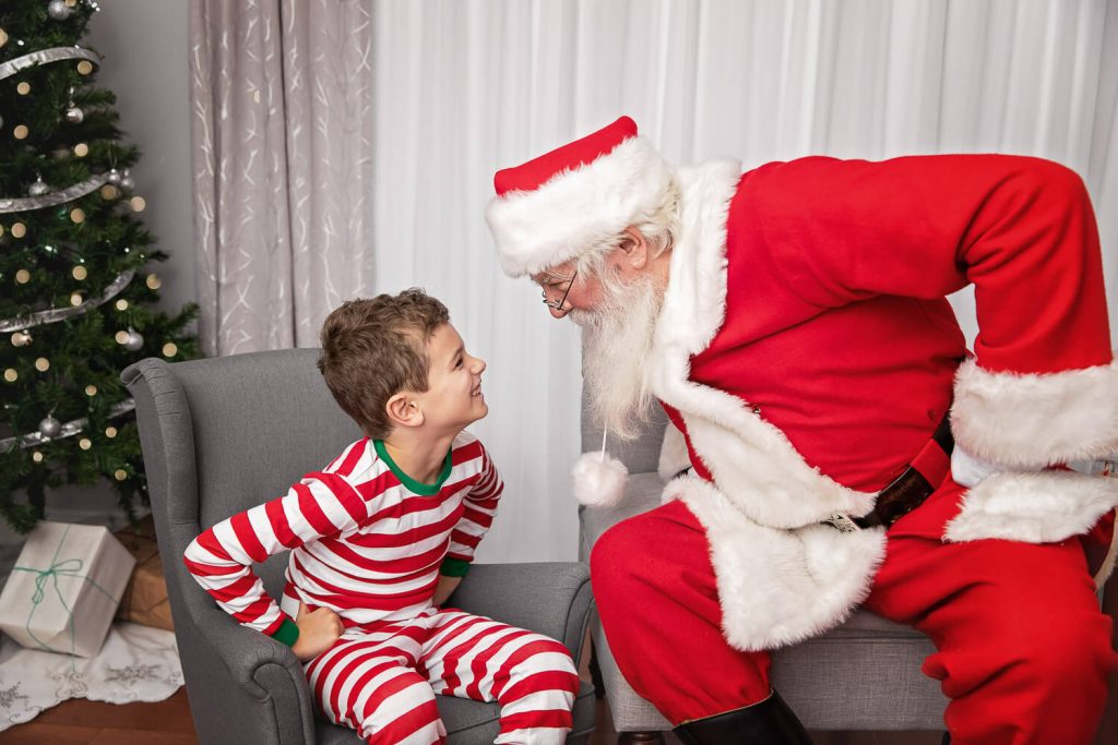 Young boy and Santa staring down each other with hands on hips