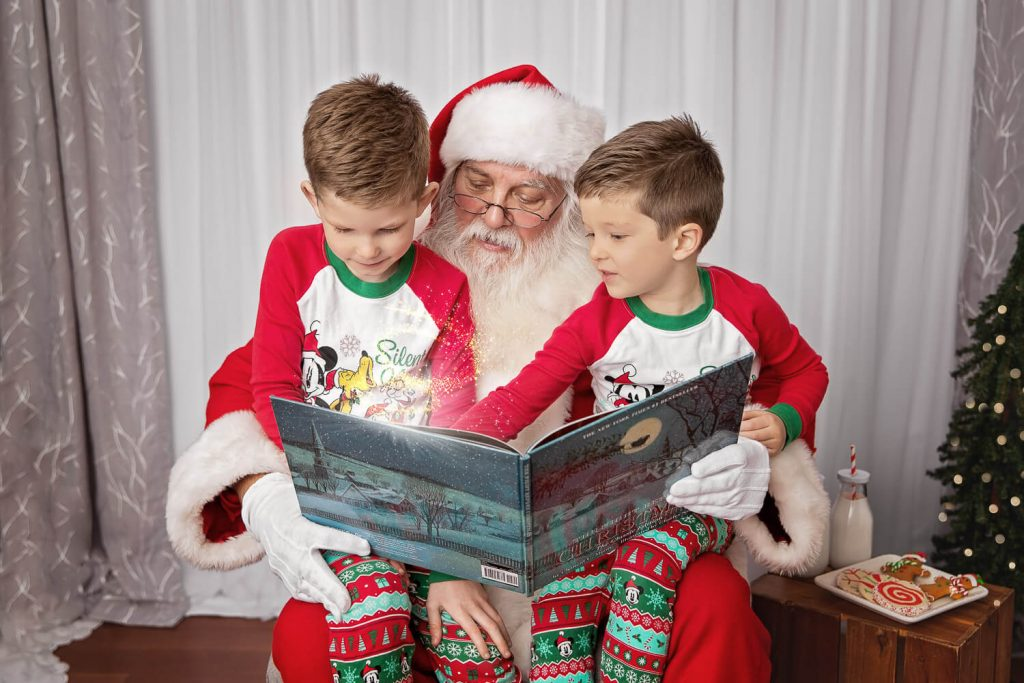 two young boys reading a book on Santa's lap with light coming out of the book