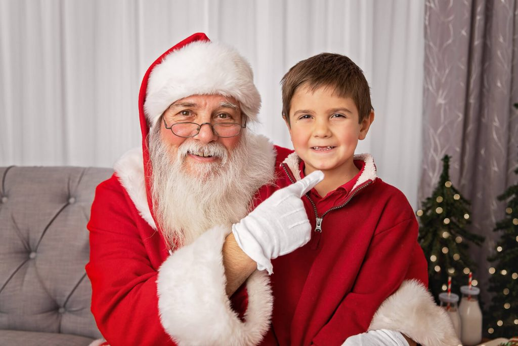 Closeup of Santa pointing to the missing front teeth of a young boy