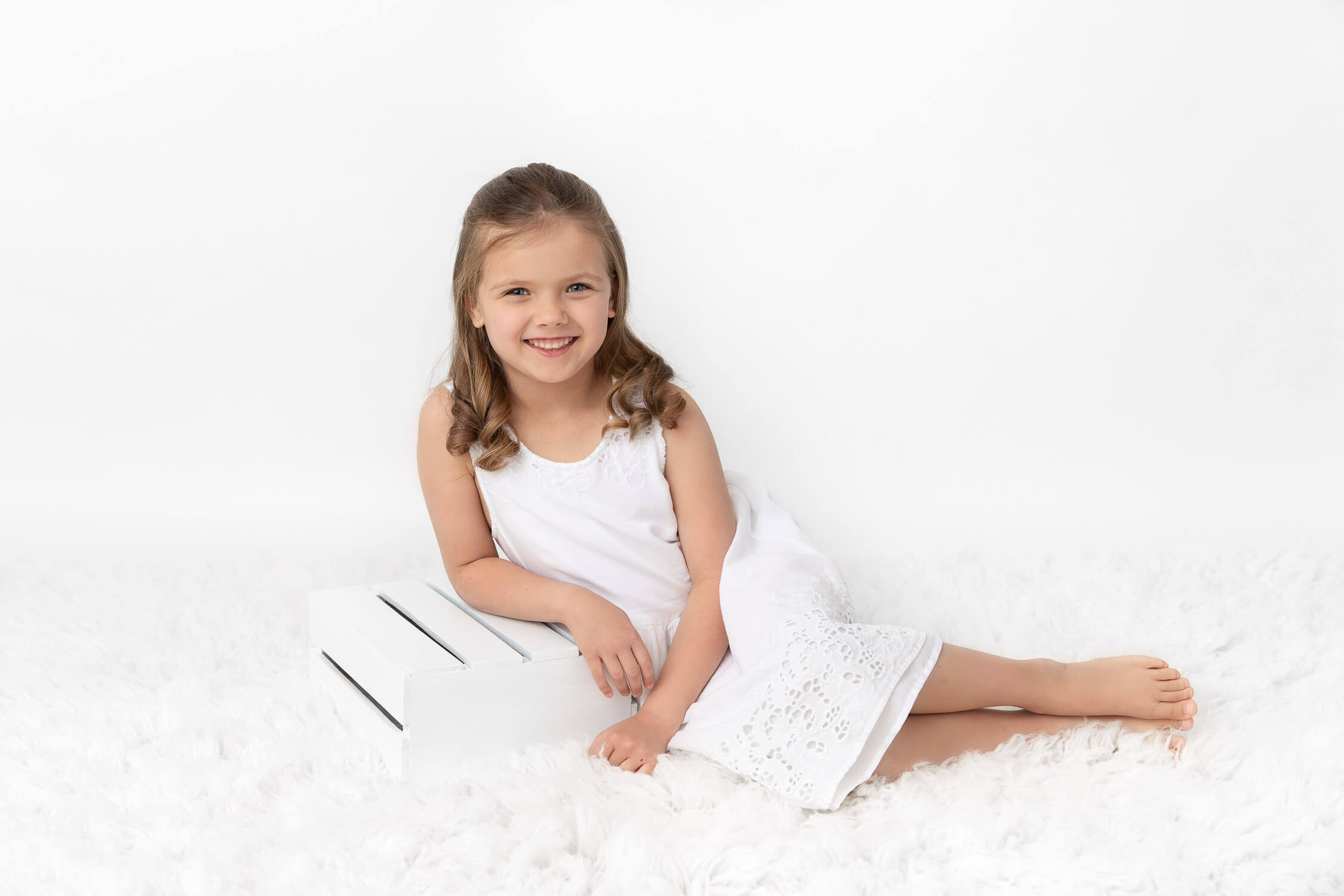 young girl wearing a white dress sitting on white fur leaning on a white crate