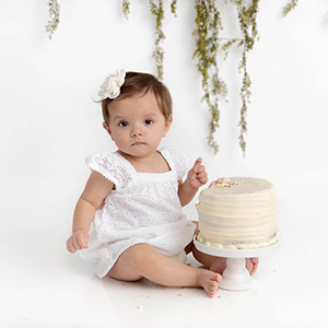 baby girl wearing a white dress with a white smash cake