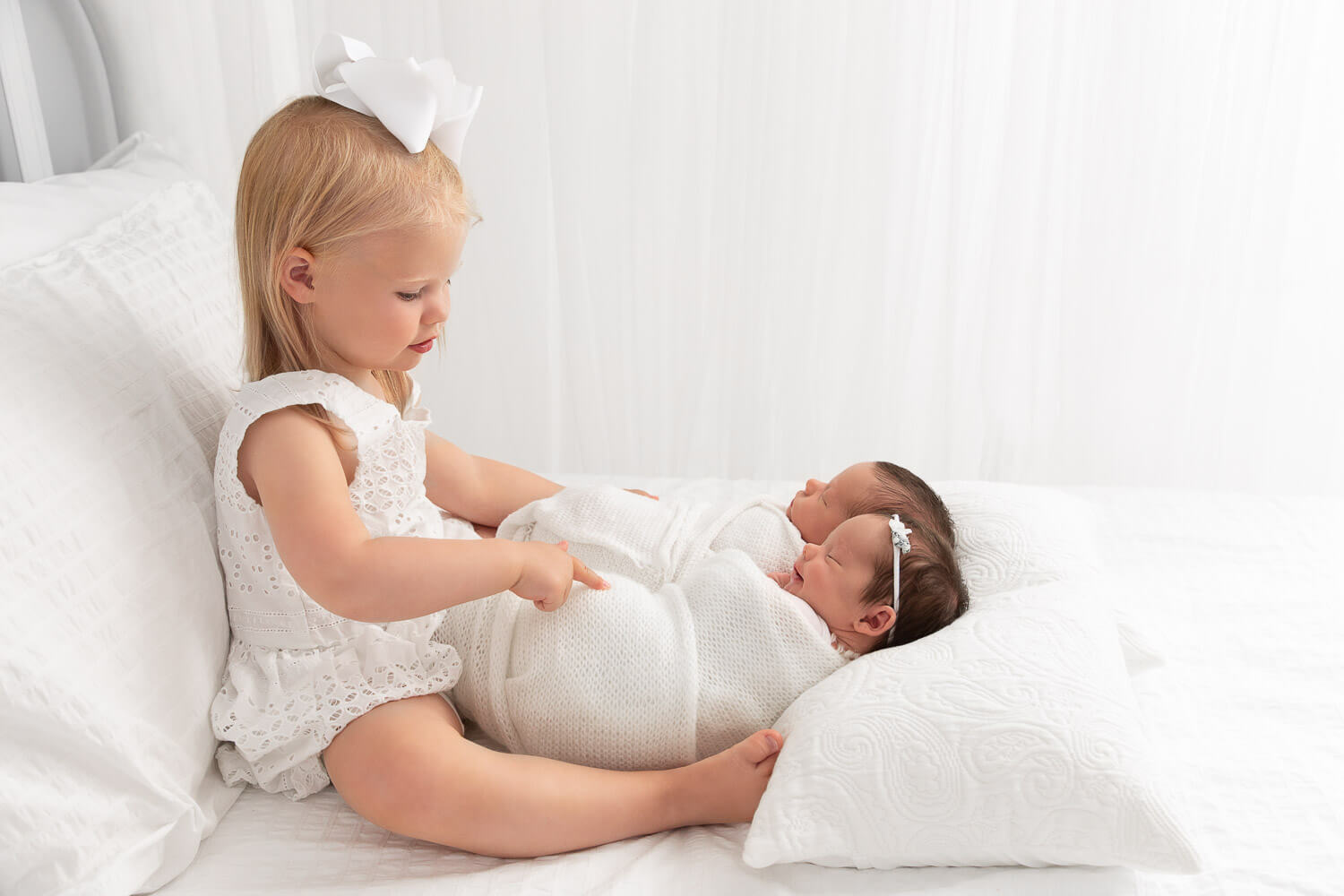 toddler girl sitting on white bed with newborn boy girl twin siblings