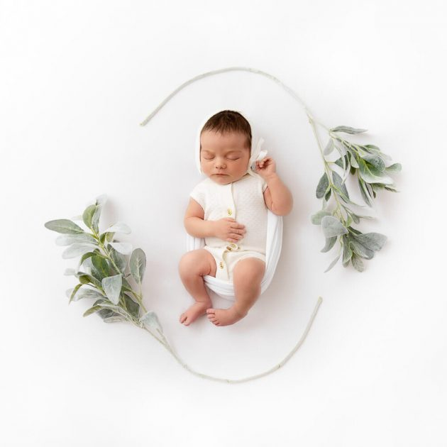 Birdseye view of baby girl wearing a white romper and bonnet on a white backdrop surrounded by lambs ear floral stems