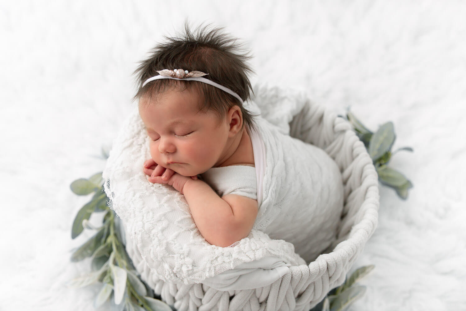 baby girl wrapped in white resting her head on hands in a white bucket on white flokati fur